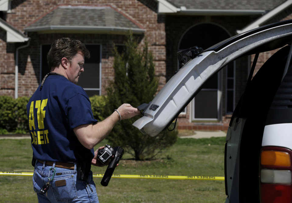 Photo - An ATF agent pulls some equipment from his vehicle as he prepares to go into the home of Kaufman District Attorney Mike McLelland Monday, April 1, 2013, near Forney, Texas. McLelland and his wife were both murdered at their home Saturday. (AP Photo/Tony Gutierrez)