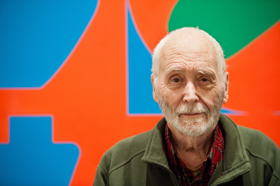 "In this Sept. 24, 2013 photo, artist Robert Indiana, known world over for his LOVE image, is interviewed in front of that painting at New York's Whitney Museum of American Art. Surrounded by 95 works he created over the past five decades, Indiana, who turned 85 this month, calls the retrospective ""a dream come true, a little late."" (AP Photo/Lauren Casselberry)"