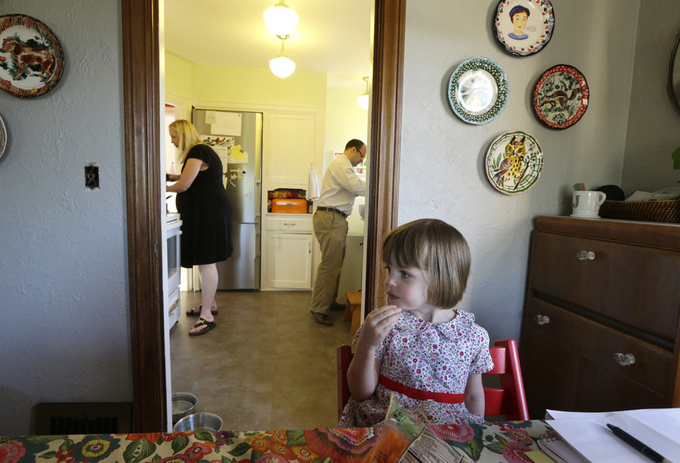 Photo - In this July 2, 2014 photo, Ryan Carson, right, cooks dinner with his wife, Jenny Roraback-Carson, left, in the kitchen while their daughter Clara, 3, has a snack in their home, in Seattle. The Carsons are one of many would-be home sellers across the country who have mortgage rates so low, it doesn't make financial sense to sell their homes, even if they need more space, a trend which limits the supply of homes and can contribute to slower home sales. (AP Photo/Ted S. Warren)