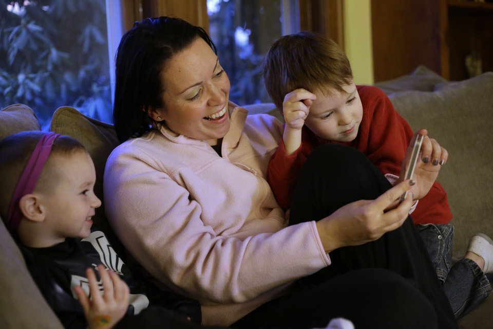 Photo - Julie Young, a Boston-based behavioral analyst, center, sits with her sons Nolan, 3, left, and Jameson, 4, right, while looking at a smart phone at their home, in Boston, Monday, Jan. 27, 2014. Child development experts say it's natural for toddlers to be fascinated with their own image, and that interest plays an important developmental role as they develop a sense of self. (AP Photo/Steven Senne)
