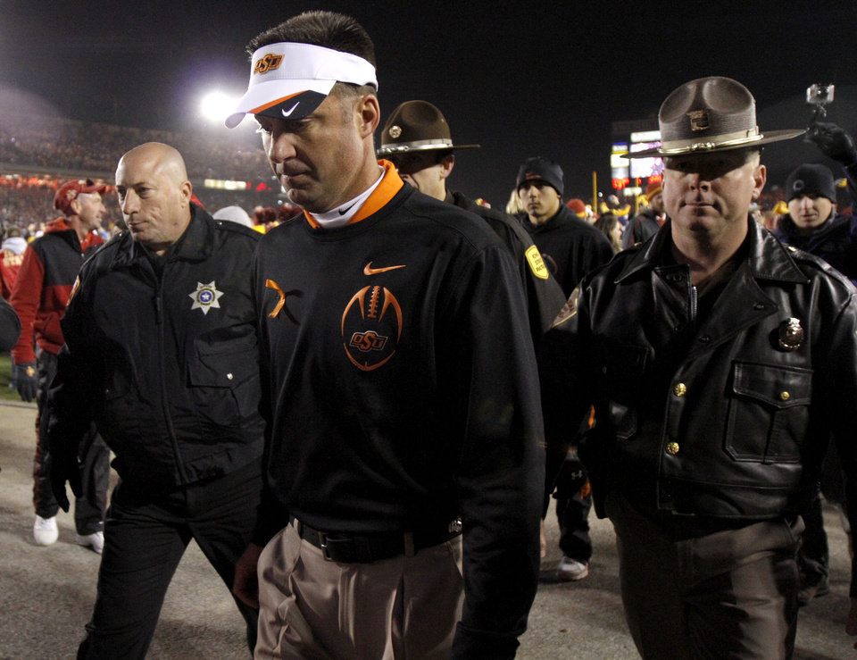 Oklahoma State coach Mike Gundy walks off the field after OSU's double-overtime loss in a college football game between the Oklahoma State University Cowboys (OSU) and the Iowa State University Cyclones (ISU) at Jack Trice Stadium in Ames, Iowa, Friday, Nov. 18, 2011. Photo by Bryan Terry, The Oklahoman