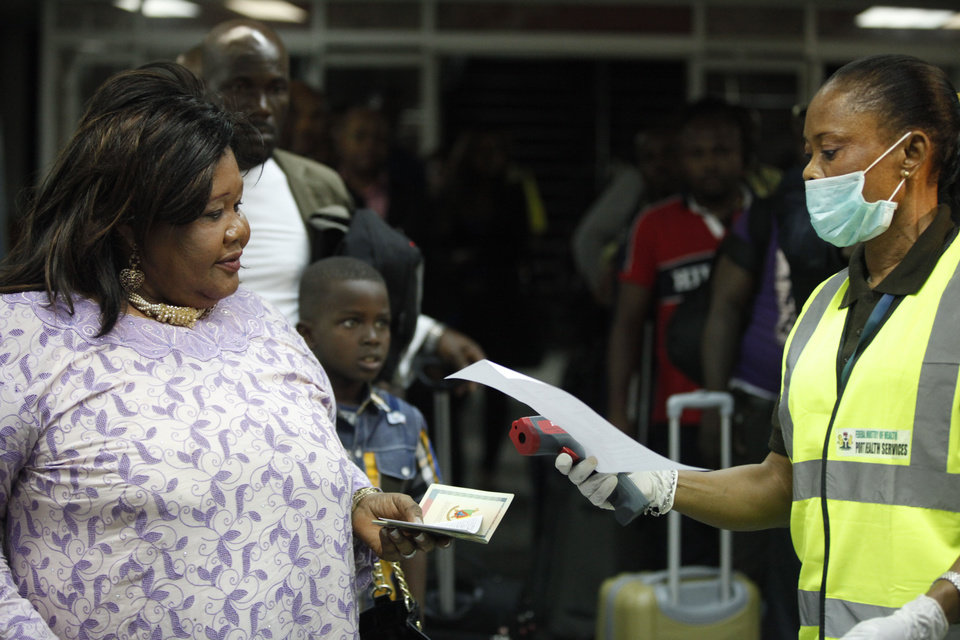 Photo - A Nigerian port health official check documents of a passenger before using a thermometer at the arrivals hall of Murtala Muhammed International Airport in Lagos, Nigeria,  Wednesday, Aug. 6, 2014. A Nigerian nurse who treated a man with Ebola is now dead and five others are sick with one of the world's most virulent diseases, authorities said Wednesday as the death toll rose to at least 932 people in four West African countries. (AP Photo/Sunday Alamba)