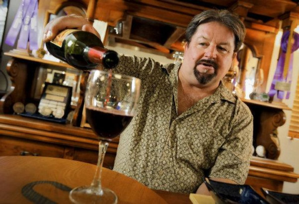 Photo - Chapel Creek Winery's Andrew Snyder pours a glass of red wine while at the tasting table at Chapel Creek Winery in El Reno. Photo by Chris Landsberger, The Oklahoman  CHRIS LANDSBERGER