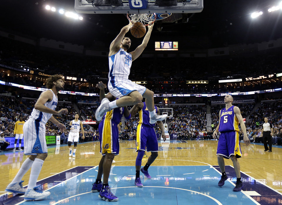 Photo - New Orleans Hornets forward Ryan Anderson (33) dunks in front of Los Angeles Lakers guard Steve Blake (5) and Hornets center Robin Lopez, left, during the first half of an NBA basketball game in New Orleans, Wednesday, March 6, 2013. (AP Photo/Gerald Herbert)