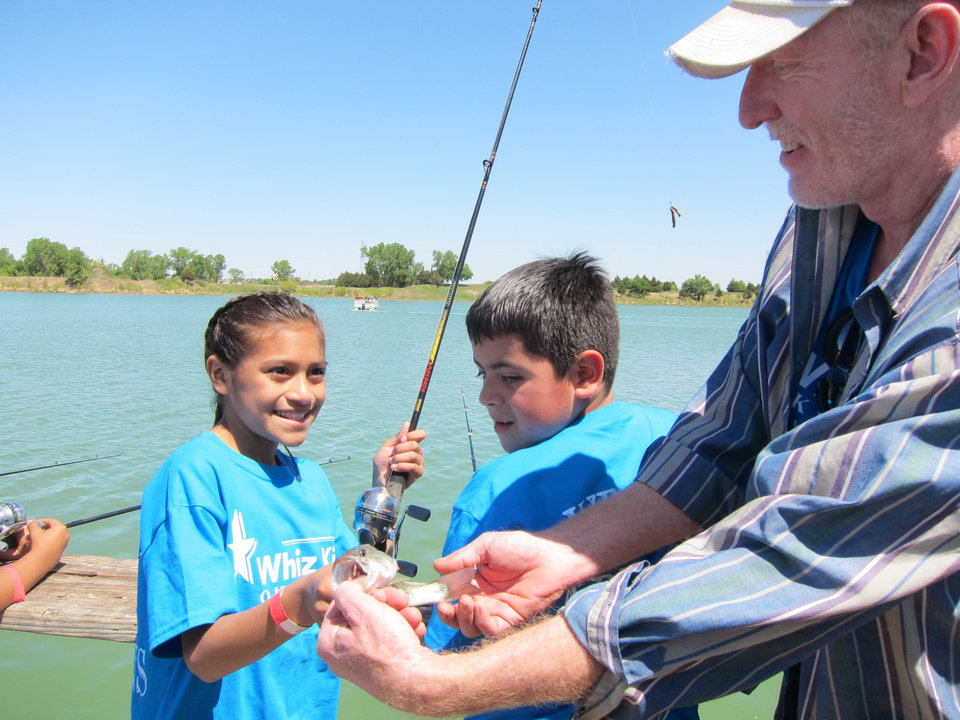 "Photo -  Jasmine Meraz, 9, left, looks at the fish she caught as it is held in the hands of Ken Greenshield, a Whiz Kids tutor from Mayflower Congregational Church, as the two join the fishing at the recent ""Spring Fling"" celebration at Crystal Lake. Photo by Carla Hinton, The Oklahoman"