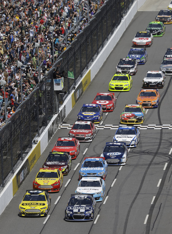 Jimmie Johnson (48) leads the pack at the start of the STP 500 NASCAR Sprint Cup series auto race at Martinsville Speedway in Martinsville, Va., Sunday April 7, 2013. (AP Photo/Steve Helber)