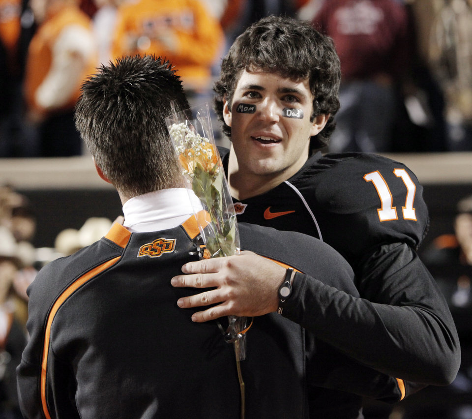 Photo - OSU's Zac Robinson (11) hugs head coach Mike Gundy as Robinson is recognized during senior night at the college football game between Oklahoma State University (OSU) and the University of Colorado (CU) at Boone Pickens Stadium in Stillwater, Okla., Thursday, Nov. 19, 2009. Photo by Nate Billings, The Oklahoman