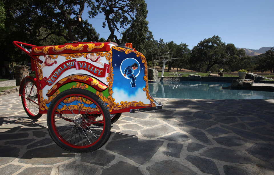 Photo - FILE - - This  July 2, 2009 file photo shows an ice cream cart given to Michael Jackson by actress Elizabeth Taylor that sits next to the pool behind the main house at the Neverland Ranch in Los Olivos, Calif. In 2014, Jackson's playtime palace sits empty now. The backyard circus and laughter of children are long gone, but the house and its fanciful memories live on.  (AP Photo/Carolyn Kaster, file)