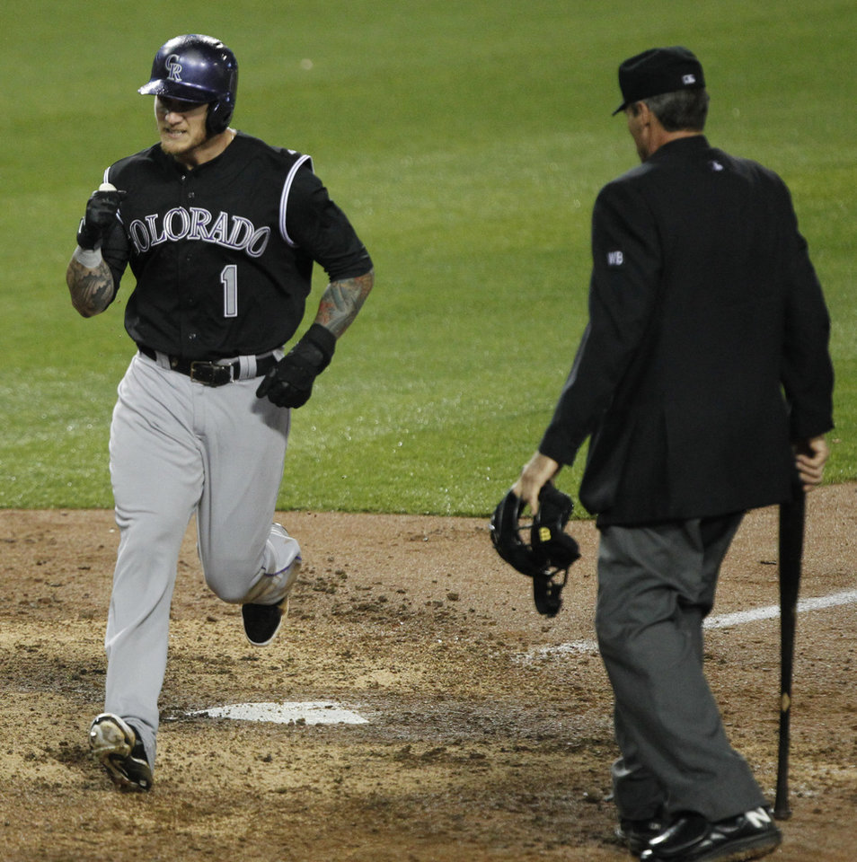 Photo - Colorado Rockies' Brandon Barnes (1) pumps his fist after scoring on a single by Rockies' Charlie Blackmon in the eleventh inning as home plate umpire Angel Hernandez, right, watches in a baseball game against the Los Angeles Dodgers on Friday, April 25, 2014, in Los Angeles. Rockies won the game 5-4 in eleven innings. (AP Photo/Alex Gallardo)