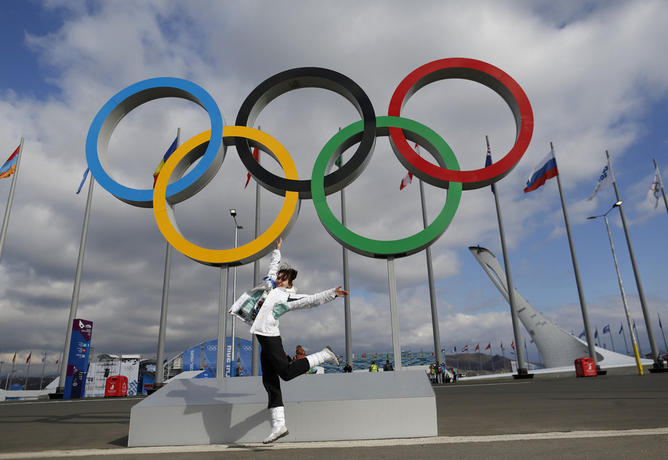 A woman jumps as she poses for a photo in front of the Olympic rings at Olympic Park ahead of the 2014 Winter Olympics, Sunday, Feb. 2, 2014, in Sochi, Russia.(AP Photo/Natacha Pisarenko)