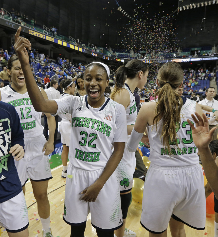 Photo - Notre Dame's Jewell Loyd (32) celebrates with teammates   after winning the NCAA college basketball championship game over Duke in the Atlantic Coast Conference tournament in Greensboro, N.C., Sunday, March 9, 2014. Notre Dame won 69-53. (AP Photo/Chuck Burton)