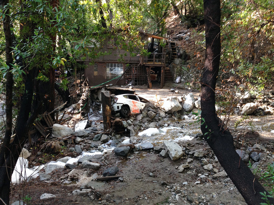 Photo - A car is lodged in the debris on Monday, Aug. 4, 2014, where a body was found Sunday that was swept into the rain-swollen water course in Mount Baldy, Calif. About 2,500 people were stranded early Monday after thunderstorms caused mountain mudslides in Southern California. (AP Photo/Brian Melley)
