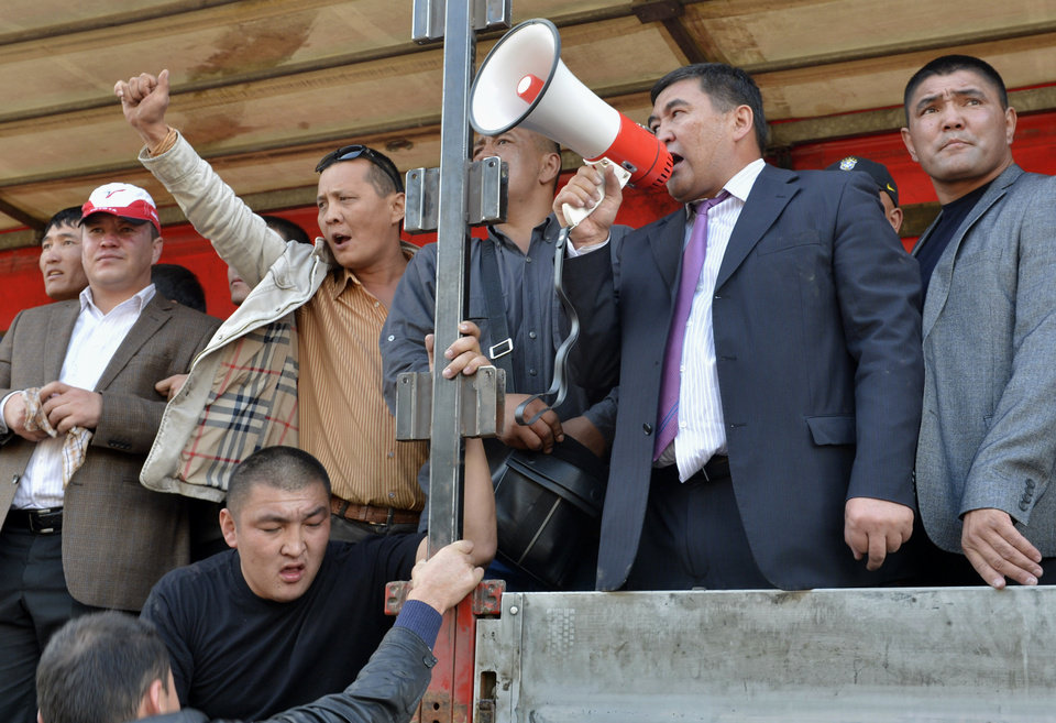 Photo -   Kamchibek Tashiyev uses a loud speaker as he adresses a crowd in downtown Bishkek, Kyrgyz capital on Wednesday, Oct. 3, 2012. Around 1,000 people gathered in the center of the city for a rally, organized by nationalist politicians Sapar Zhaparov and Kamchibek Tashiyev, ostensibly to demand the nationalization of a controversial gold mine in the east of the Central Asian nation. Police officers protecting the government building, known as the White House, used dogs and smoke bombs to disperse a group of young men who attempted to scale the gates. (AP Photo/ Vladimir Voronin)