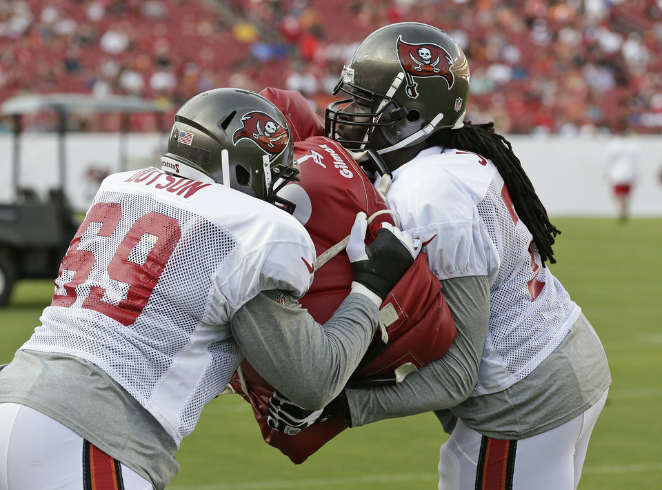 Tampa Bay Buccaneers guard Davin Joseph (a former Sooner), right, blocks tackle Demar Dotson during the NFL football team's training camp Saturday, July 27, 2013, in Tampa, Fla. (AP Photo/Chris O'Meara)