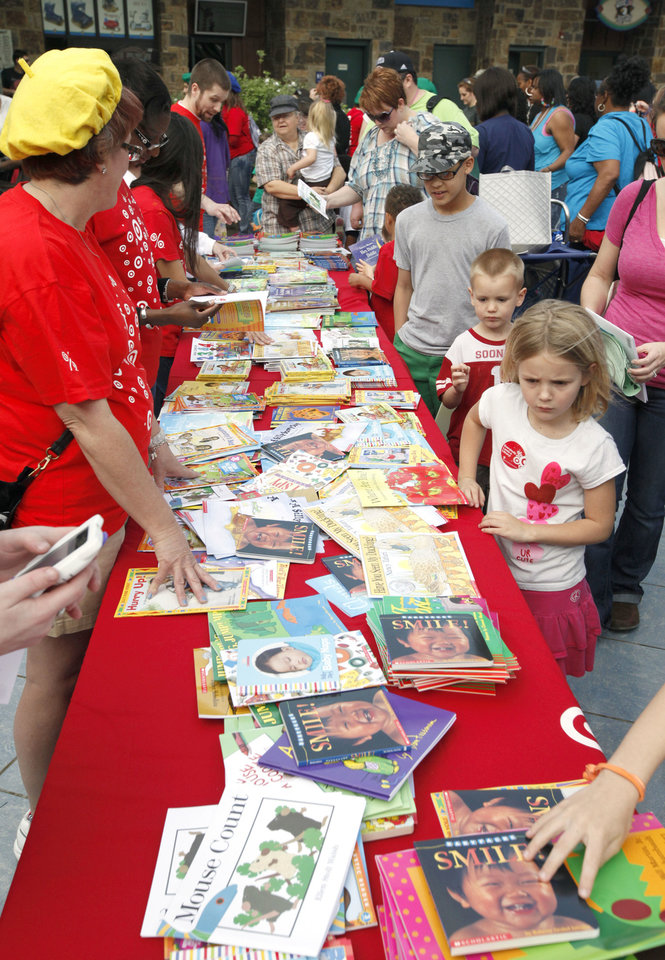 Photo - Above: Children look through hundreds of books during Read Across Oklahoma on Tuesday at the Oklahoma City Zoo.
