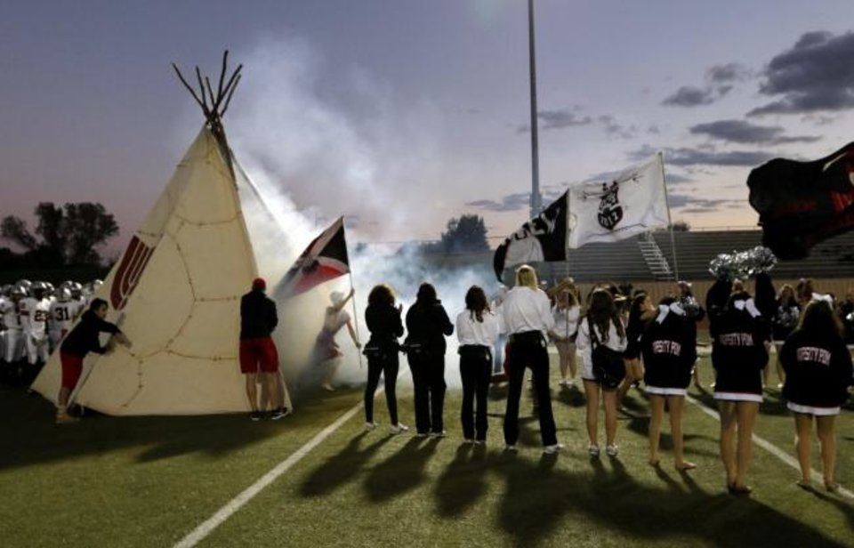 Photo -  The Tulsa Union football team runs out of a teepee before a 2016 game at Southmoore. [OKLAHOMAN ARCHIVES]