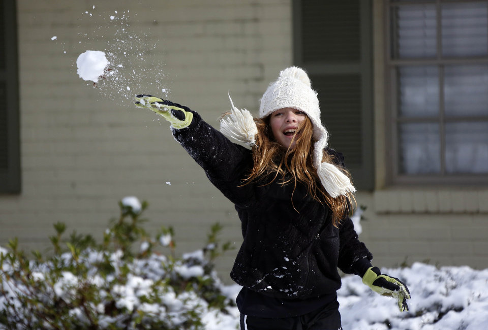Photo - Skylar Alexander, 11, of Jackson, Miss.,  tosses a snowball at her brother Thursday,  Jan. 17, 2013.  A winter storm system left 2 to 4 inches of snow in parts of central Mississippi before heading east toward Alabama, the National Weather Service said. (AP Photo/Rogelio V. Solis)