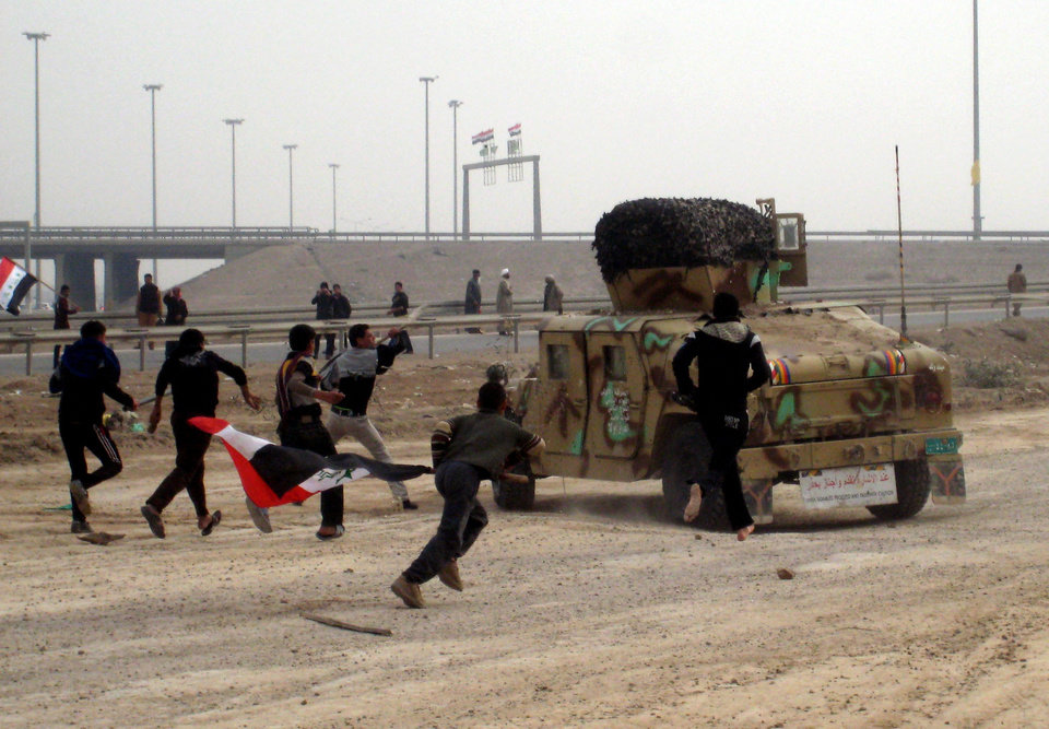 Protesters throw stones towards Iraqi soldiers at a checkpoint during clashes in Fallujah, 40 miles (65 kilometers) west of Baghdad, Iraq, Friday, Jan. 25, 2013. Iraqi troops shot dead five protesters Friday as they opened fire at stone-hurling demonstrators angry at the troops for preventing them from joining an anti-government rally west of Baghdad, officials said. (AP Photo/ Bilal Fawzi)