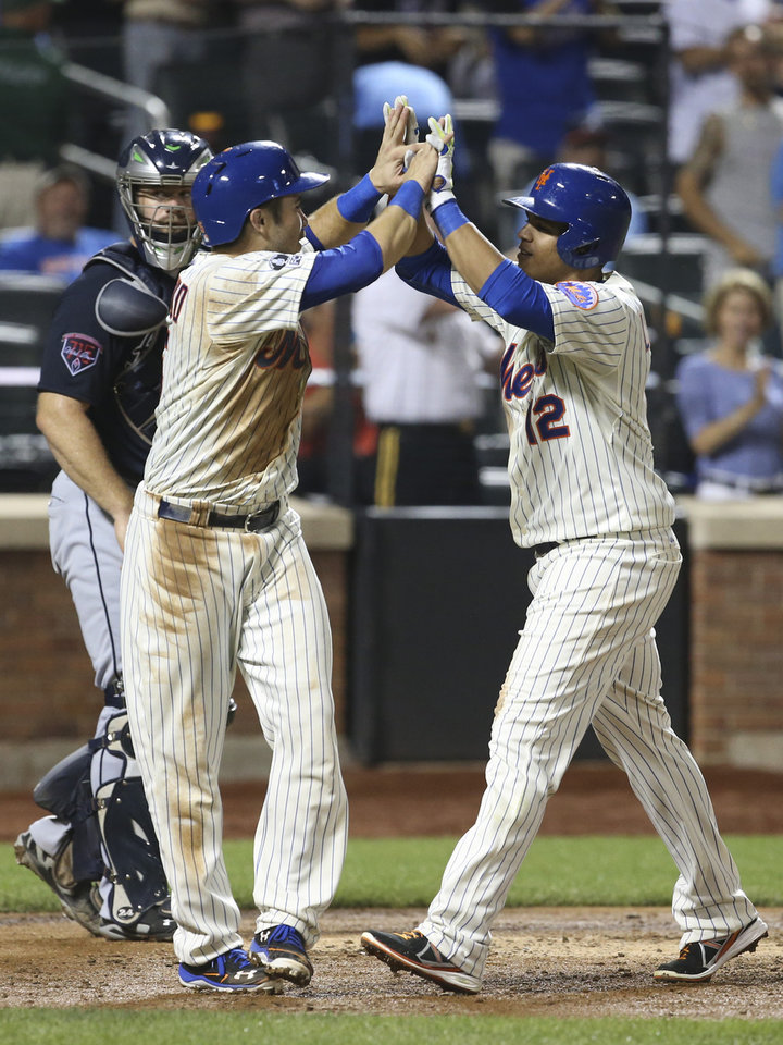 Photo - New York Mets Juan Lagares (12) celebrates alongside Travis d'Arnaud after hitting a two-run home run in the fourth inning of a baseball game against the Atlanta Braves on Tuesday, Aug. 26, 2014, in New York. (AP Photo/John Minchillo)