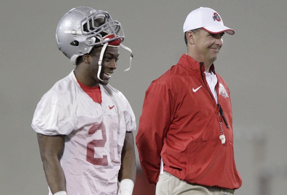 Photo - Ohio State coach Urban Meyer, right, laughs with cornerback Armani Reeves during NCAA college football practice Tuesday, March 4, 2014, in Columbus, Ohio. (AP Photo/Jay LaPrete)