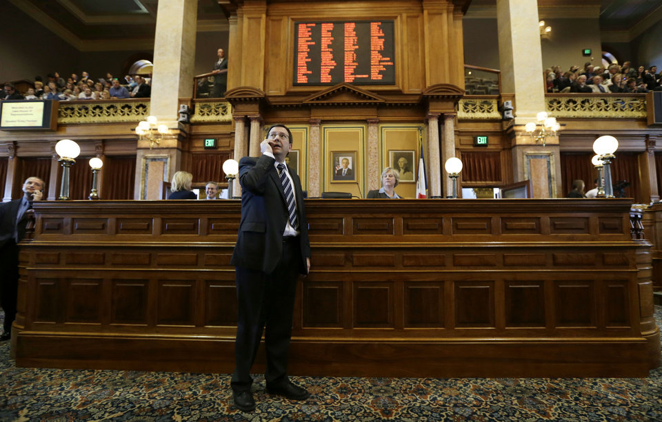 Photo - Iowa Speaker of the House Kraig Paulsen talks on his cell phone during the opening day of the Iowa Legislature, Monday, Jan. 14, 2013, at the Statehouse in Des Moines, Iowa. (AP Photo/Charlie Neibergall)