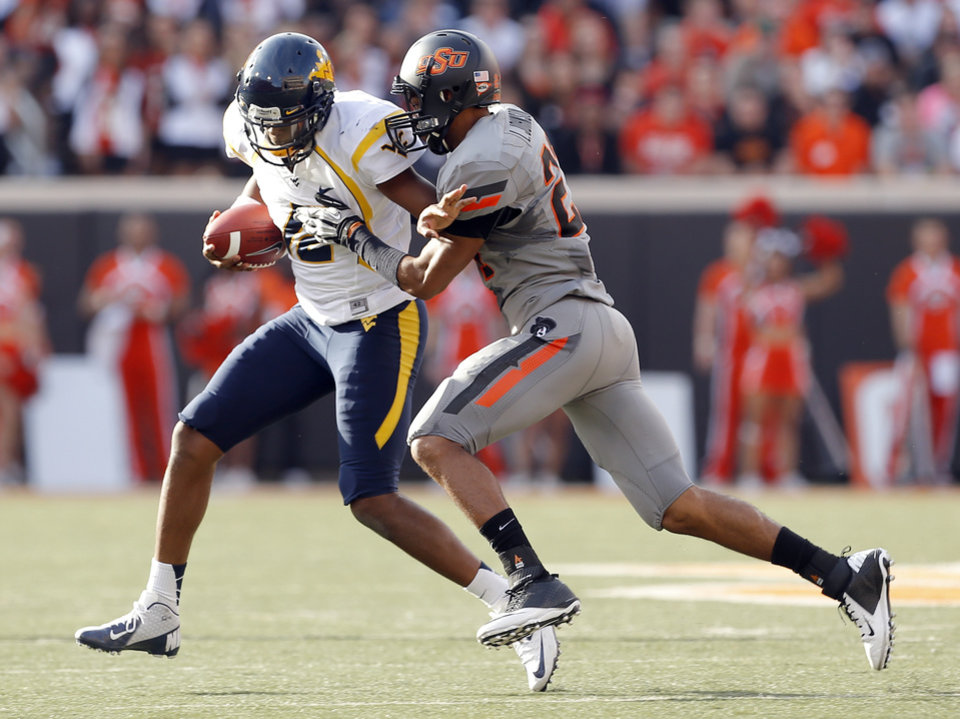 Photo - Oklahoma State's Lyndell Johnson (27) tackles West Virginia's Geno Smith (12) as he scrambles during a college football game between Oklahoma State University (OSU) and the West Virginia University at Boone Pickens Stadium in Stillwater, Okla., Saturday, Nov. 10, 2012. OSU won 55-34. Photo by Sarah Phipps, The Oklahoman