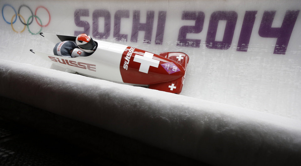 Photo - The team from Switzerland SUI-1, piloted by Beat Hefti and brakeman Alex Baumann, take a curve during the men's two-man bobsled competition at the 2014 Winter Olympics, Sunday, Feb. 16, 2014, in Krasnaya Polyana, Russia. (AP Photo/Natacha Pisarenko)