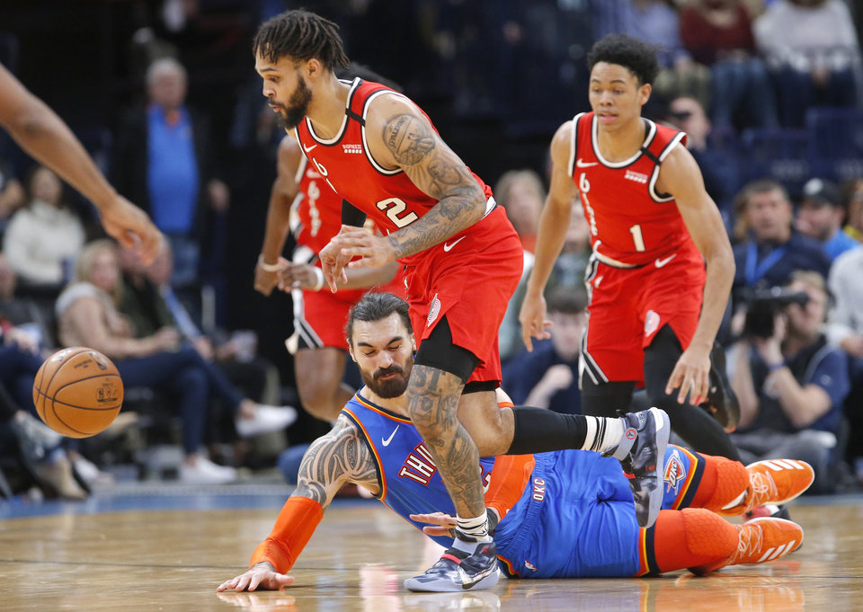 Photo - Oklahoma City's Steven Adams (12) falls to the ground after fighting for a loose ball with Portland's Gary Trent Jr. (2) during the NBA basketball game between the Oklahoma City Thunder and the Portland Trail Blazers at the Chesapeake Energy Arena in Oklahoma City, Saturday, Jan. 18, 2020.  [Sarah Phipps/The Oklahoman]