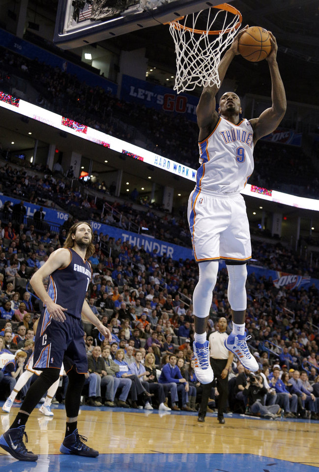 Photo - Oklahoma City's Serge Ibaka (9) dunks in front of Charlotte's Josh McRoberts (11) during the NBA basketball game between the Oklahoma City Thunder and the Charlotte Bobcats at the Chesapeake Energy Arena, Sunday, March 2, 2014. Photo by Sarah Phipps, The Oklahoman
