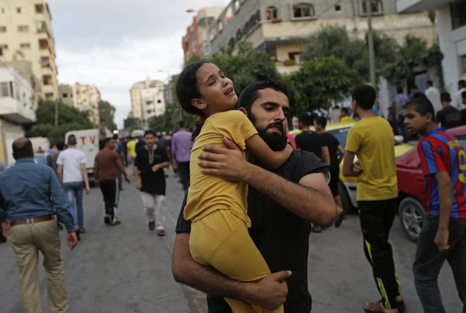 Photo - A Palestinian man carries away a girl, that was overcome by emotion, during the funeral  of Muhammed Abu Shagfa, 7, killed in an explosion, in Shati refugee camp, in the northern Gaza Strip, Monday, July 28, 2014. An explosion killed 10 people, 9 of them children, at a park at Shati refugee camp, in northern Gaza Strip. Israeli and Palestinian authorities traded blame over the attack and fighting in the war raged on despite a major Muslim holiday. (AP Photo/Lefteris Pitarakis)