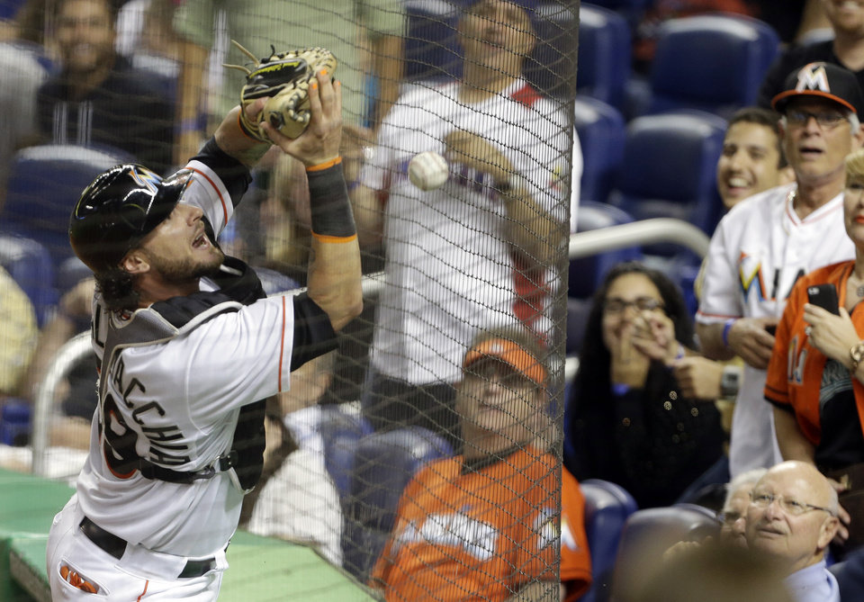 Photo - Miami Marlins catcher Jarrod Saltalamacchia can't come up with the ball on a foul hit by Anthony Rendon during the sixth inning of a baseball game, Wednesday, April 16, 2014, in Miami. (AP Photo/Lynne Sladky)