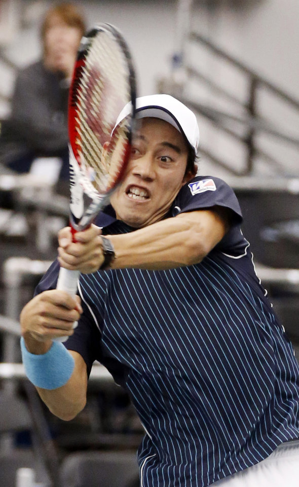 Kei Nishikori,of Japan, hits a return to Ivo Karlovic, of Croatia, in the singles final at the U.S. National Indoor Tennis Championships on Sunday, Feb. 16, 2014, in Memphis, Tenn. (AP Photo/Rogelio V. Solis)