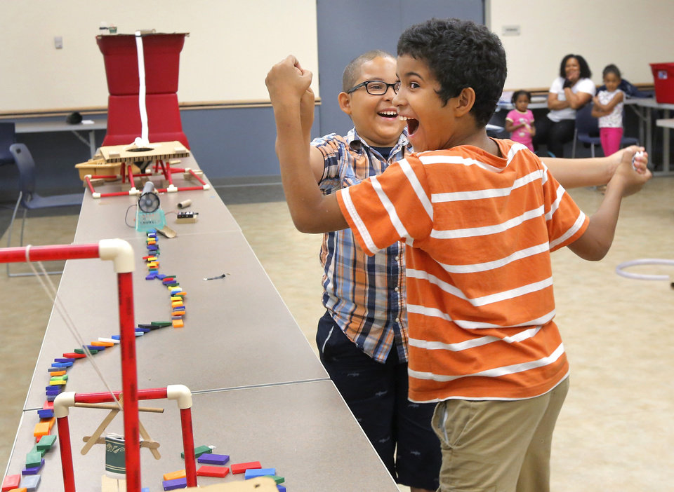 "Photo -  Brothers Mateo Linden, 10, left, and Tre Linden, 11, erupt into a celebration after their experiment in toppling all the dominoes is successful at an ""Imagineering"" camp at Ralph Ellison Library. Photo by Jim Beckel, The Oklahoman   Jim Beckel -"
