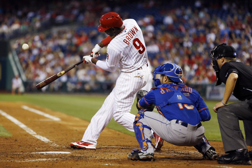 Photo - Philadelphia Phillies' Domonic Brown hits a three-run home run off New York Mets starting pitcher Rafael Montero during the fourth inning of a baseball game, Friday, May 30, 2014, in Philadelphia. At center is catcher Travis d'Arnaud and at right is umpire Cory Blaser. (AP Photo/Matt Slocum)