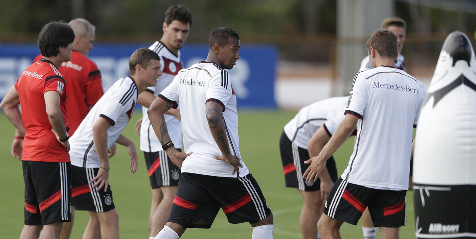 Photo - German national soccer player Jerome Boateng, center, talks to Thomas Mueller, right, during a training session in Santo Andre near Porto Seguro, Brazil, Saturday, June 14, 2014. Germany will play in group G of the 2014 soccer World Cup. (AP Photo/Matthias Schrader)