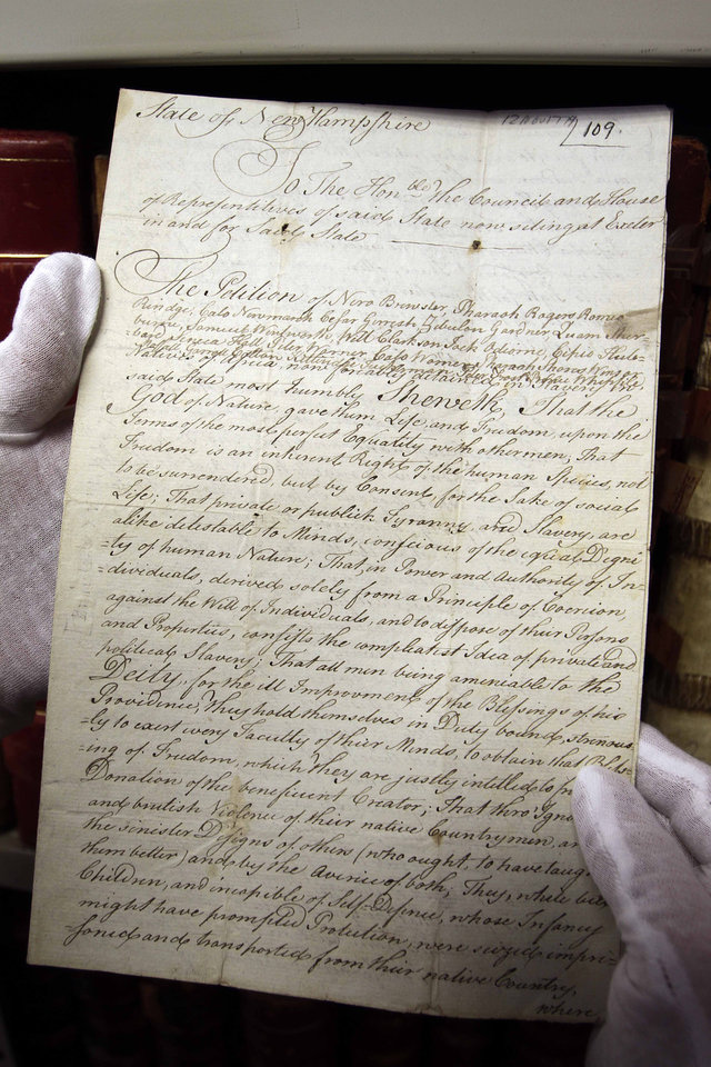 A section of a petition filled by 20 African slaves asking for their freedom more than 200 years ago is seen at the New Hampshire state Archives Wednesday March 7, 2013 in Concord, N.H. New Hampshire lawmakers are considering a bill that would posthumously grant the request of African slaves who petitioned for their freedom during the Revolutionary War. (AP Photo/Jim Cole)