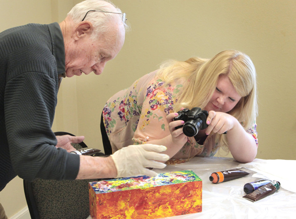 John Lawton paints as University of Central Oklahoma senior Amy Griffin takes photos  at the Edmond Senior Center.