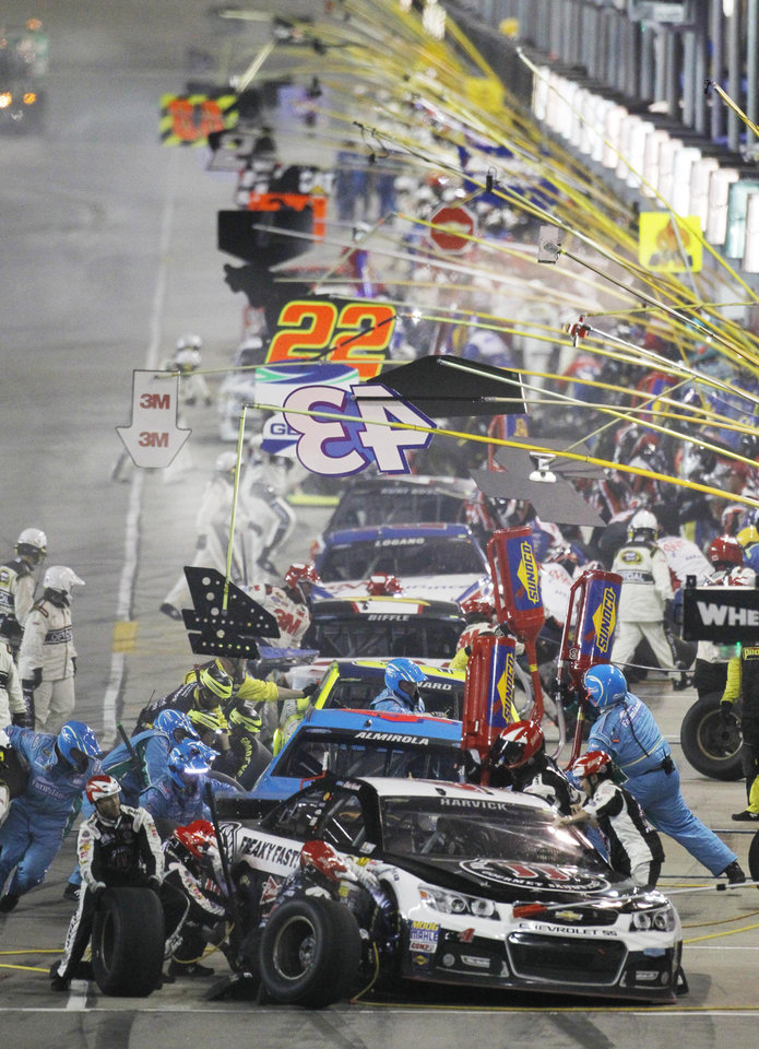 Photo - NASCAR driver Kevin Harvick (4) heads the line of teams making a pit stop during the Sprint Cup Series auto race at Kansas Speedway in Kansas City, Kan., Saturday, May 10, 2014. (AP Photo/Colin E. Braley)