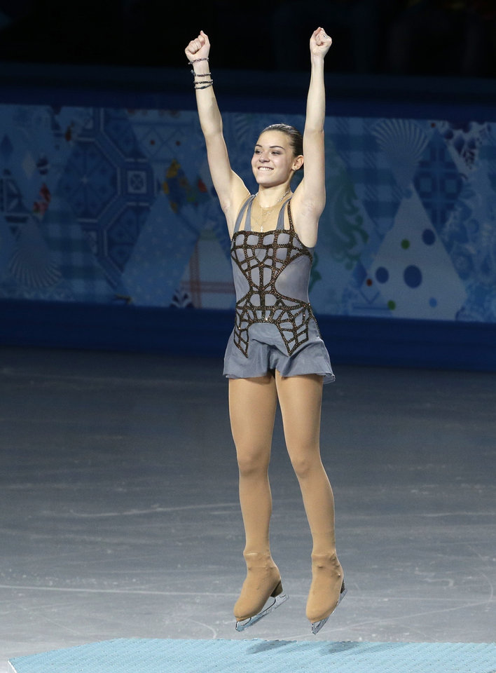 Photo - Adelina Sotnikova of Russia jumps on the podium as she celebrates placing first during the flower ceremony for the women's free skate figure skating final at the Iceberg Skating Palace during the 2014 Winter Olympics, Thursday, Feb. 20, 2014, in Sochi, Russia. (AP Photo/Darron Cummings)