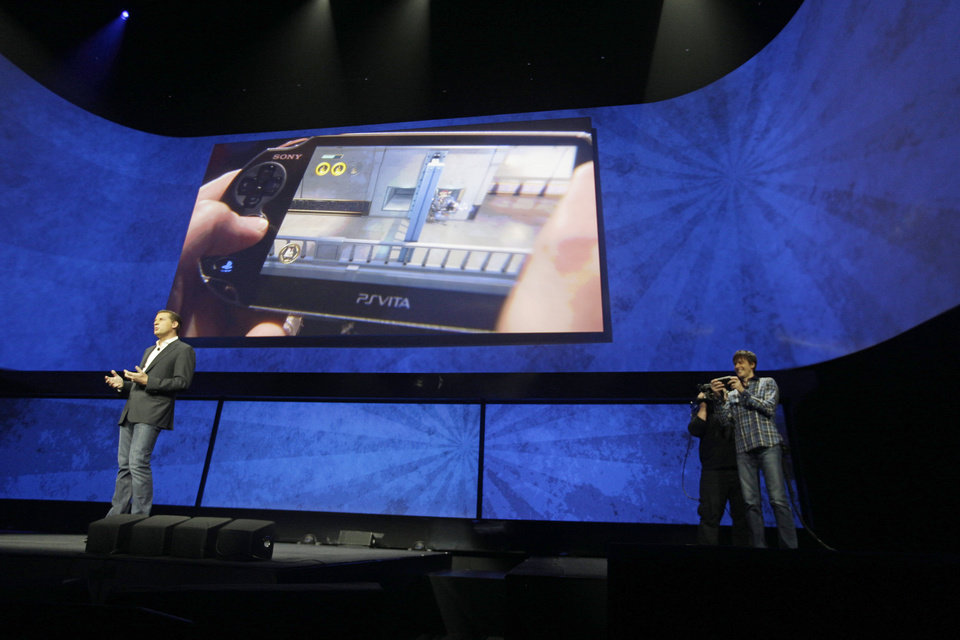David Perry, CEO of Gaikai, left, speaks as Mark Cerny, demonstrates remote game play on the PSVita during a news conference to announce the Sony Playstation 4 Wednesday, Feb. 20, 2013, in New York.  (AP Photo/Frank Franklin II)