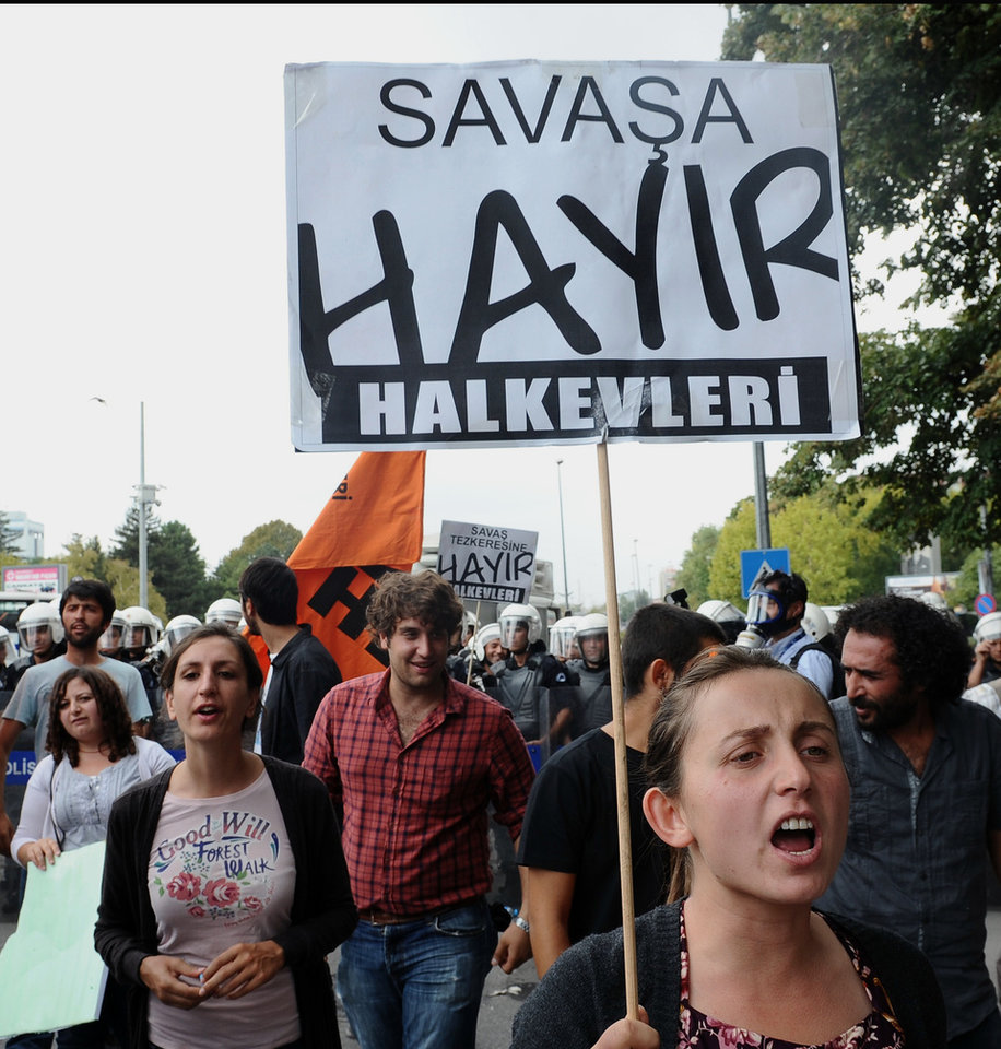 Photo -   Turks hold banners that read