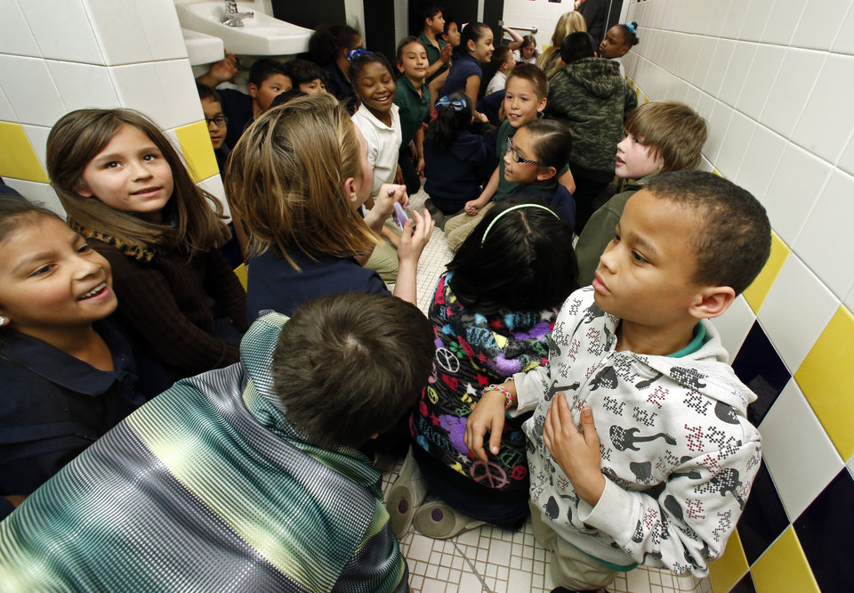 """Photo - Arthur Elementary third-graders get up from  their """"duck and cover"""" posture in storm preparation assembly areas on Tuesday, April 1, 2014 in Oklahoma City, Okla.  Photo by Steve Sisney, The Oklahoman"""
