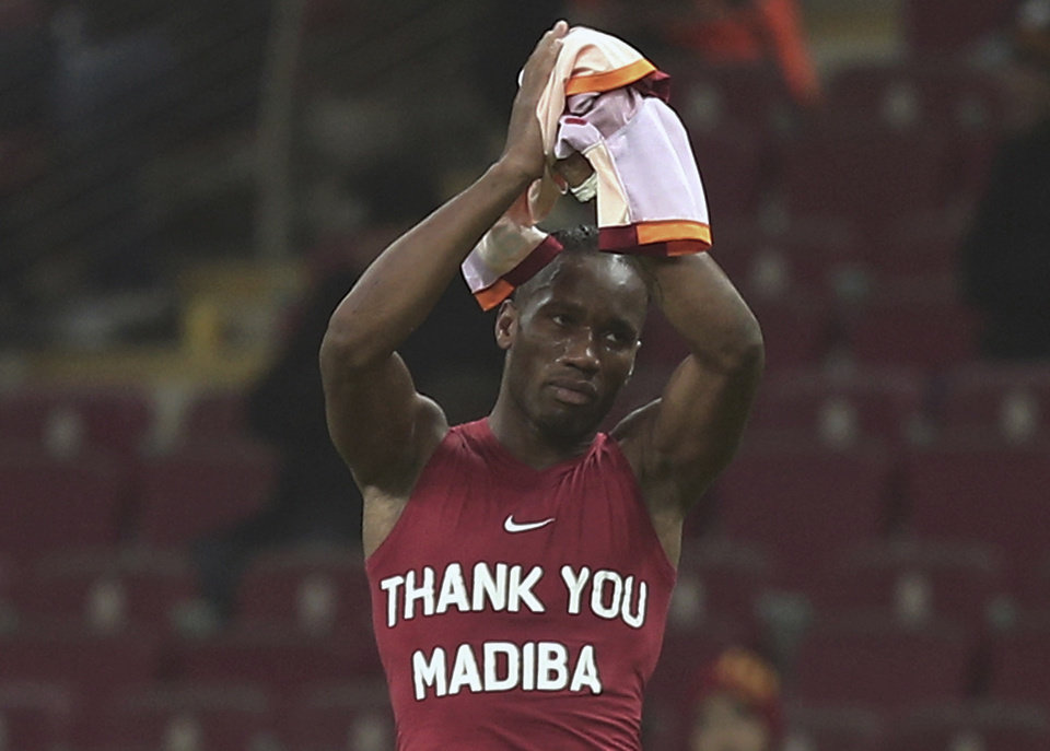 Photo - FILE - This is a Friday, Dec. 6, 2013 file photo of   Galatasaray's Didier Drogba from Ivory Coast salutes soccer fans as he wears a jersey in sign of respect for Nelson Mandela before their Turkish League match with Elazigspor in Istanbul, Turkey. The International Football Association Board  (IFAB)  could make a clear ruling to crack down on players revealing personal messages on their undershirts, especially during goal celebrations.  The current laws of football prohibit a player revealing political slogans or advertising on an undershirt, and a proposed new wording would ban any kind of personal text or image.  (AP Photo/File)