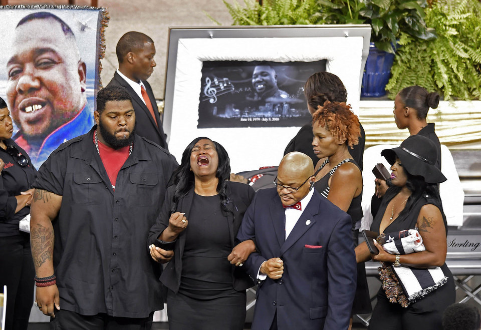 Photo - Sandra Sterling, an aunt who helped raise Alton Sterling, sobs as she is helped away from the casket during visitation before the funeral service fot Sterling at the F.G. Clark Activity Center in Baton Rouge, La., Friday, July 15, 2016. Sterling was shot July 5 outside a Baton Rouge convenience store in an encounter with police that was caught on video. (Travis Spradling/The Advocate via AP)