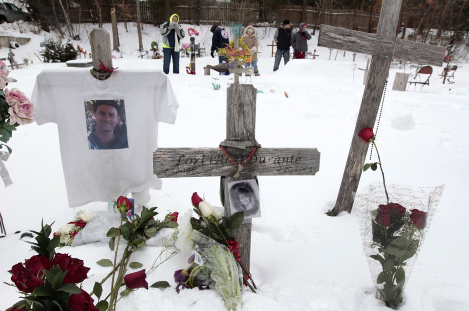 Photo - Mourners for those killed in The Station nightclub fire stand among makeshift memorials on the site of the fire, Sunday, Feb. 17, 2013, in West Warwick, R.I. The Station Fire Memorial Foundation unveiled final plans to build a permanent memorial at the site during ceremonies Sunday. The 2003 blaze, which broke out when pyrotechnics for the rock band Great White ignited flammable packing foam that had been installed inside the club as soundproofing, took the lives of 100 people. (AP Photo/Steven Senne)