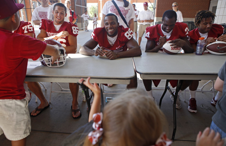 Photo - From  left, OU's James Winchester, Ryan Broyles, Dejuan Miller, and Trey Franks sign autographs during the University of Oklahoma's Meet the Sooners Day at Gaylord Family-Oklahoma Memorial Stadium in Norman, Okla., Saturday, August 6, 2011. Photo by Bryan Terry, The Oklahoman