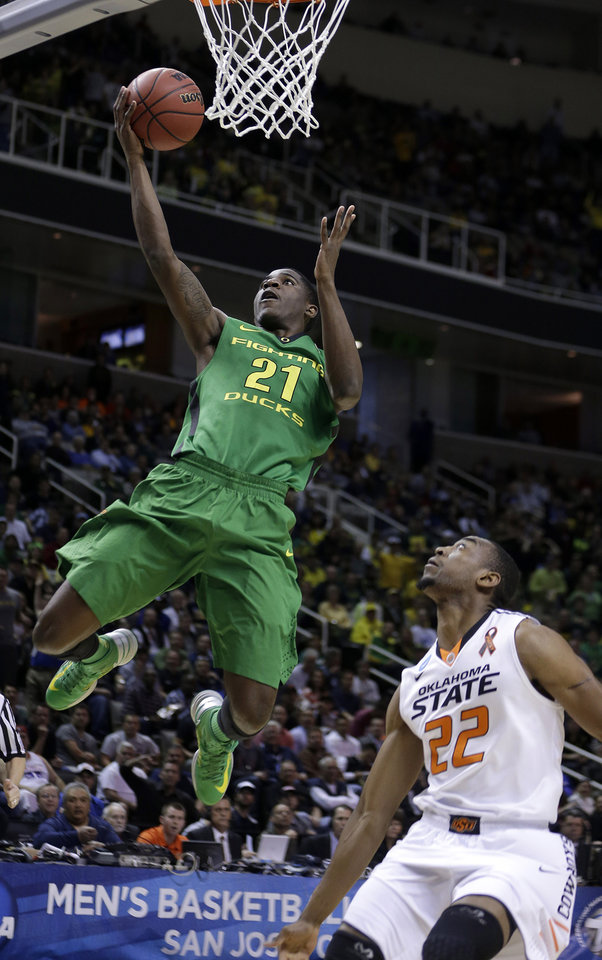 Oregon guard Damyean Dotson (21) shoots over Oklahoma State guard Markel Brown (22) during the first half of a second-round game in the NCAA college basketball tournament in San Jose, Calif., Thursday, March 21, 2013. (AP Photo/Ben Margot) ORG XMIT: SJA118