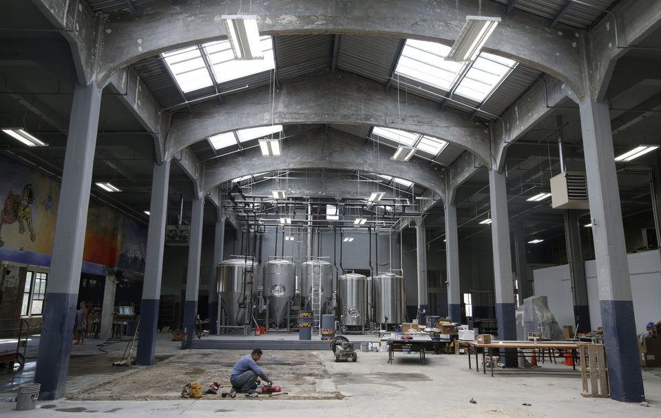 Photo - Workers put the finishing touches on the tap room in the Rhinegeist brewery, Wednesday, June 19, 2013, in Cincinnati. Rhinegeist is set to open to the public June 29 in what used to be part of the old Christian Moerlein complex. (AP Photo/Al Behrman)