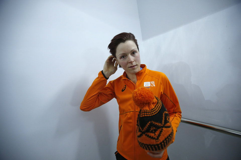Photo - Gold medallist Jorien ter Mors of the Netherlands holds her cap and stands by the side prior to the flower ceremony for the women's 1,500-meter speedskating race at the Adler Arena Skating Center during the 2014 Winter Olympics in Sochi, Russia, Sunday, Feb. 16, 2014. (AP Photo/Pavel Golovkin)