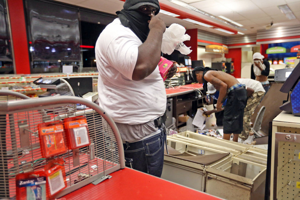 Photo - People are seen in a store Sunday, Aug. 10, 2014, in Ferguson, Mo. A few thousand people crammed a suburban St. Louis street Sunday night at a vigil for unarmed 18-year-old Michael Brown shot and killed by a police officer, while afterward several car windows were smashed and stores were looted as people carried away armloads of goods as witnessed by an an Associated Press reporter. (AP Photo/St. Louis Post-Dispatch, David Carson)